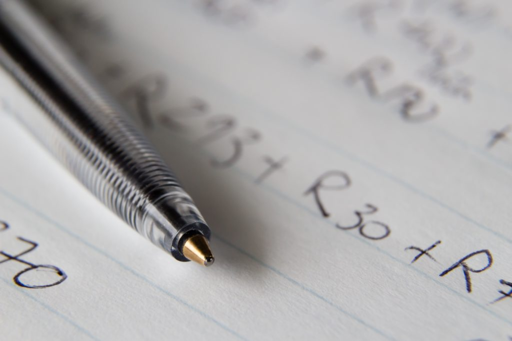 stylo avec papier et calculs scientifiques : la diversification financière demande un niveau en mathématiques.